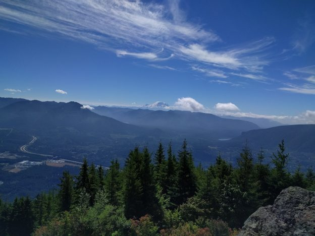 From atop Mount Si, a blue sky, green trees, and Mt. Rainier in the distance.